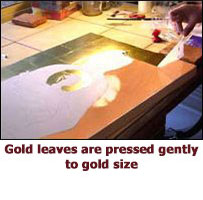 Gold leaves are pressed gently to gold size